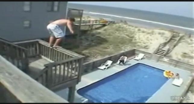 Un joven, en pleno salto a una piscina desde un balcón.