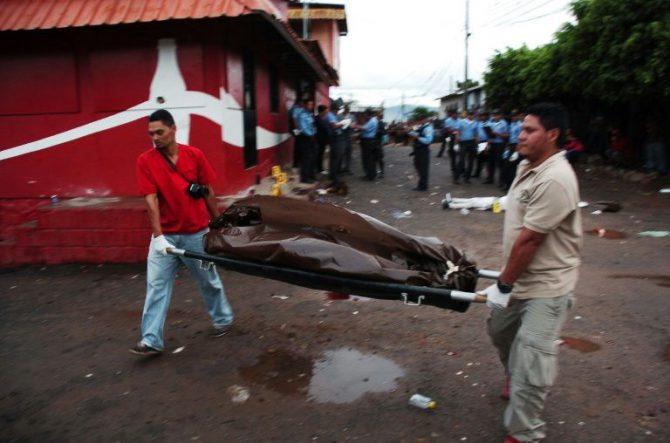 Personal forense traslada el cuerpo de uno de los ocho jóvenes asesinados en una tienda el 14 de agosto de 2016 en Tegucigalpa