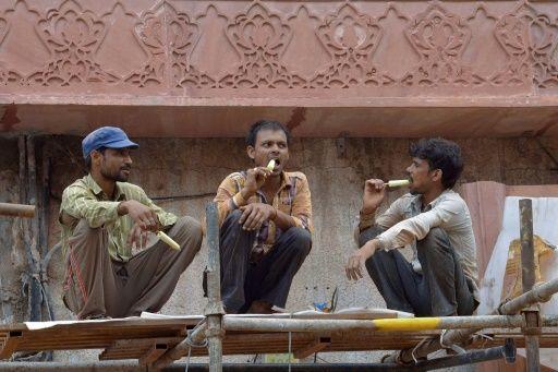 Trabajadores indios comen helados durante un descanso del trabajo en Amritsar, el 30 de julio de 2016