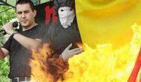Otegui interviniendo en un acto mientras un encapuchado quema una bandera española.