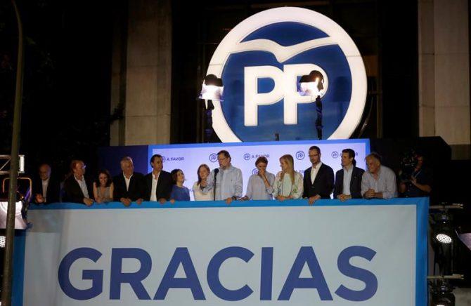 El presidente del gobierno en funciones Mariano Rajoy, acompañado por miembros del PP, se dirige a los simpatizantes populares concentrados en la Calle Génova de Madrid, tras conocer los resultados electorales del 26J.