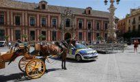 La Policía Local de Sevilla ha detenido a un hombre de unos 40 años después de apuñalar mortalmente a otro en pleno centro sevillano. En la fotografía, un coche de patrulla de la policía estacionado al lado de un coche de caballos en Sevilla.