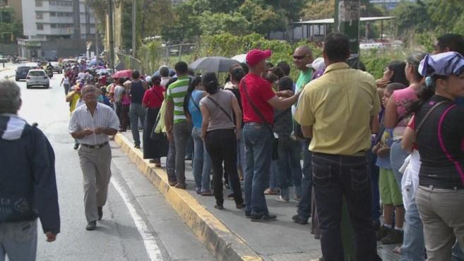 Larga cola para comprar en un supermercado de Caracas.