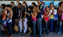 La gente forma filas para comprar alimentos y productos básicos fuera de un supermercado en Caracas.