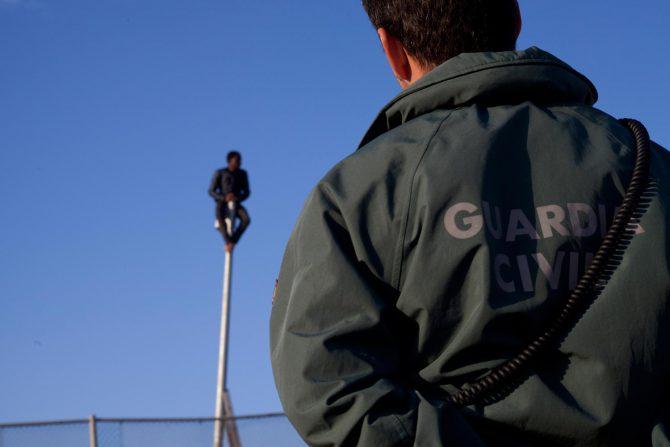 Un guardia civil observa a un subsahariano subido a un poste de la valla de Melilla.
