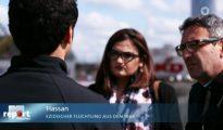 Hasan (izquierda), un refugiado yazidí en Alemania que ha sido amenazado por musulmanes, cuenta a un reportero de la televisión estatal germana cómo el traductor a sueldo del Estado tradujo mal deliberadamente su denuncia y se puso de parte de los atacantes. (Imagen: captura de un vídeo de Bayerischer Rundfunk)