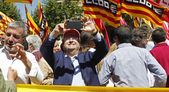 Miquel Iceta haciendo una foto, en una manifestación contra la suspensión de varias leyes catalanas.