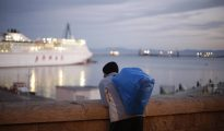 Un joven marroquí observa un barco a punto de partir del puerto de Melilla.