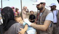 Voluntarios de la Organización No Gubernamental 'Doctores de Chipre' atienden a un niño en el campo de refugiados instalado en la isla de Chios, Grecia.