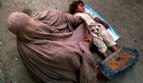 Una mujer con burka y su hija piden limosna en una calle de Peshawar (Pakistán).