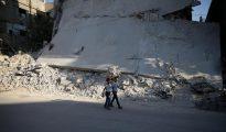 Dos niños caminan junto a un edificio bombardeado en un barrio rebelde de Damasco