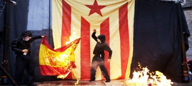 Dos miembros de la CUP quemando imágenes del Rey y banderas de España.