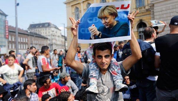Amores que matan: Un refugiado sirio exhibe una fotografía de Angela Merkel.