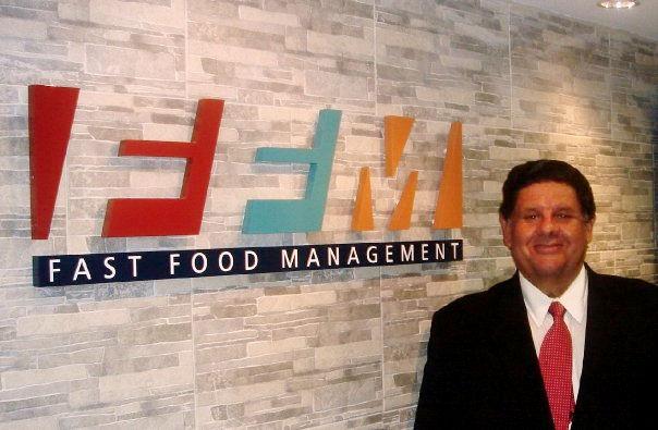 John A. Regis posa junto al logo de una de sus empresas.