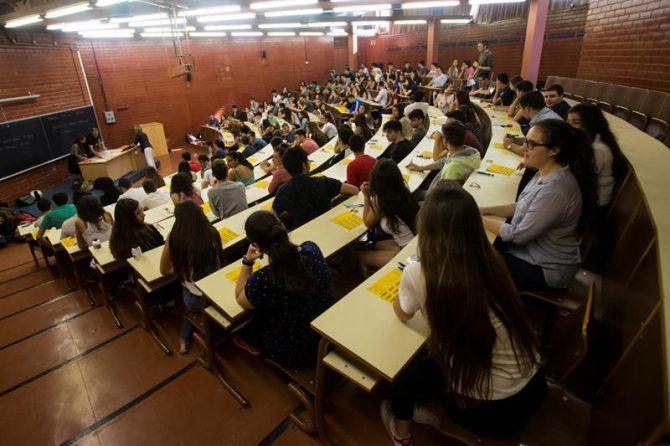 Unos estudiantes atienden a las instrucciones en una Facultad.