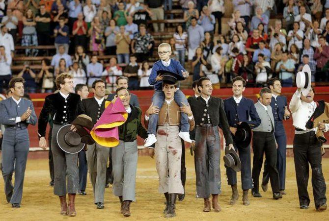 Adrián, un niño de ocho años con cáncer y que sueña con ser torero, es llevado a hombros por los toreros que han participado esta tarde en festival celebrado en la Plaza de toros de Valencia en su homenaje.