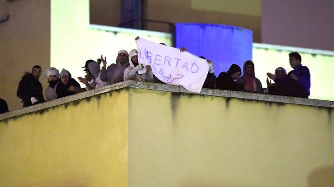 """Los ilegales amotinados con un cartel reclamando """"libertad""""."""