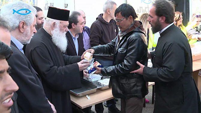 """El arzobispo Jerónimo de Atenas y toda Grecia distribuye comida a migrantes en el puerto del Pireo. El arzobispo se quitó el crucifijo durante su visita al Pireo, para, dijo, no """"ofender"""" a los migrantes musulmanes. (Imagen: pantallazo de un vídeo de Hellas News TV)"""