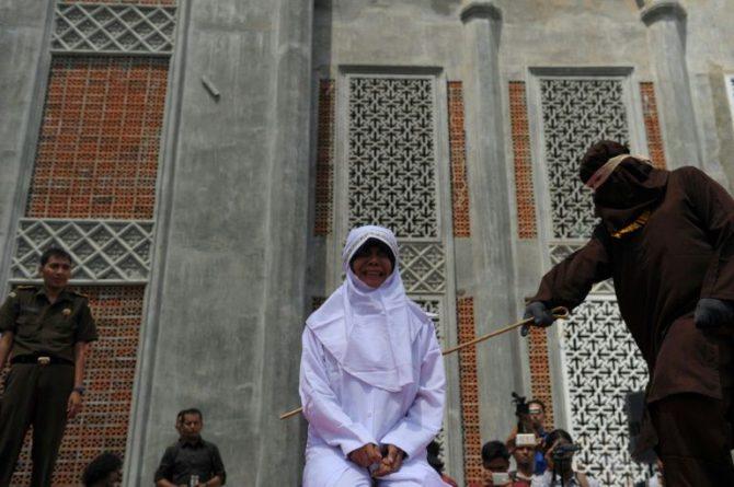 Un oficial religioso azota a una mujer castigada por tener una cita fuera del matrimonio, contraviniendo la ley islámica o sharia, el 1 de agosto de 2016 fuera de la mezquita de Banda Aceh, en Indonesia