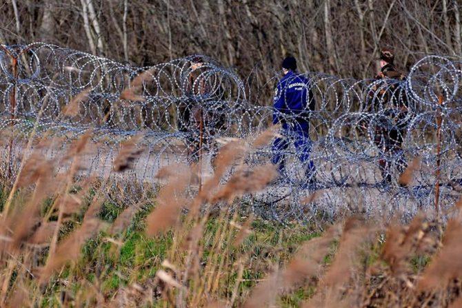 Policías y soldados húngaros patrullan junto a la valla temporal que separa la frontera entre Serbia y Hungría, en Hajdukovo, Serbia.