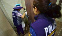 """Una integrante del equipo de """"caza de cámaras ocultas"""" de Seúl (i) y una agente de policía inspeccionan un baño de mujeres en un museo de la ciudad el 18 de agosto de 2016"""