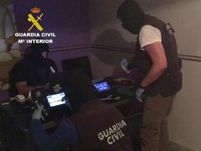 Imagen de vídeo facilitada por la Guardia Civil, de tres agentes de la Benemérita analizando los dispositivos electrónicos que han inautado hoy a dos imanes marroquíes, que han sido detenidos hoy en Ibiza por su presunto apoyo al grupo terrorista Estado Islámico (EI).