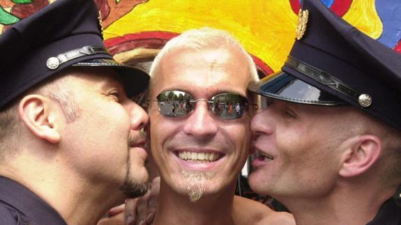 Dos gais vestidos de policías besan a un compañero durante el desfile del 'Christopher Street Day' en Berlín.