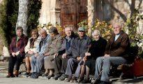 Varios ancianos toman el sol.