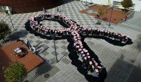 Estudiantes forman un lazo rosa durante un Día Mundial del Cáncer de Mama.