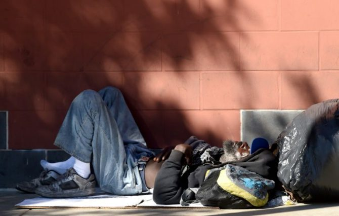 Un hombre sin hogar duerme al lado de una pared en la acera a lo largo de una calle en el centro de Los Angeles, California, el 9 de febrero de 2016