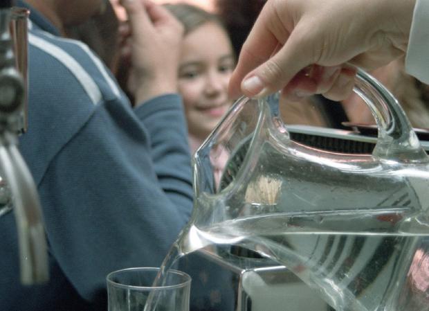 Un camarero sirve un vaso de agua