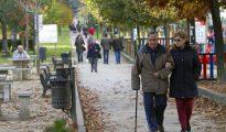 Un hombre y una mujer pasean por un parque de Vigo.