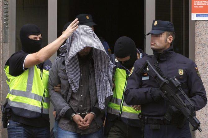 Agentes del Cuerpo Nacional de Policía trasladan a un hombre de orígen marroquí, que ha sido detenido hoy en Gijón en el marco de una operación antiyihadista, al que se considera miembro de una red de propaganda y captación del Dáesh.