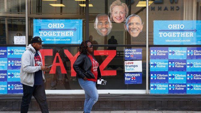 Dos personas pasan junto a un establecimiento que distribuye entradas para un concierto de apoyo a la candidata demócrata a la presidencia de EE.UU., Hillary Clinton, en Cleveland, Ohio.
