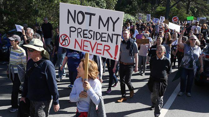 Una mujer sostiene un cartel durante una manifestación contra el Presidente electo Donald Trump en Golden Gate Park, San Francisco (California).