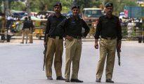 Policías paquistaníes hacen guardia cerca del lugar de un atentado contra un vehículo de las fuerzas de seguridad en la ciudad Fateh Jang, Pakistán