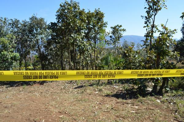 Policías de la Fuerza Estatal acotan el lugar donde peritos forenses trabajan sobre el hallazgo de unas 20 fosas clandestinas, en el municipio de Zitlala, del estado mexicano de Guerrero