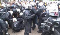 Policías alemanes tratan de detener una pelea masiva entre migrantes. (Imagen tomada de un vídeo de SAT1).