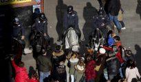 Agentes de la Policía Nacional montados a caballo en la Puerta del Sol llena de gente en estas fechas navideñas