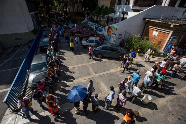 Un grupo de personas hace fila en las inmediaciones del Banco Central de Venezuela este viernes 16 de diciembre del 2016, en Caracas