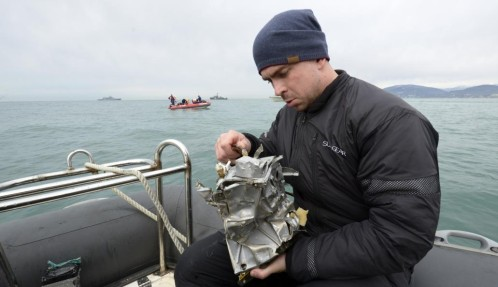 Un integrante del servicio de emergencias ruso inspecciona uno de los restos del fuselaje rescatado del mar Negro