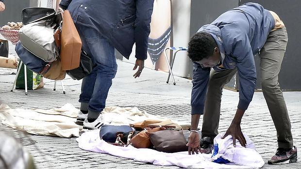 Dos manteros en plena huida, recogen sus artículos antes de que llegue la Policía
