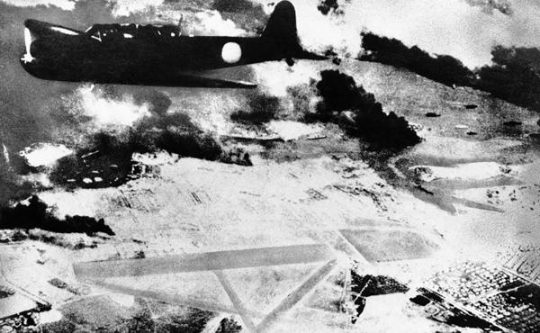 Un bombardero japonés sobre Pearl Harbour, mientras el humo negro ya sale de los barcos estadounidenses