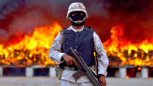 Un soldado custodia la quema de paquetes de marihuana en Tijuana, en cotubre de 2010