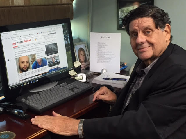 John Regis posa junto a una portada de Alerta Digital.