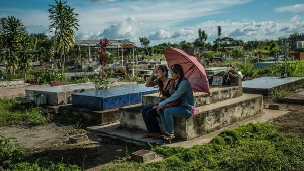 Yamilet Lugo (izquierda) llora frente la tumba de su hijo Kevin