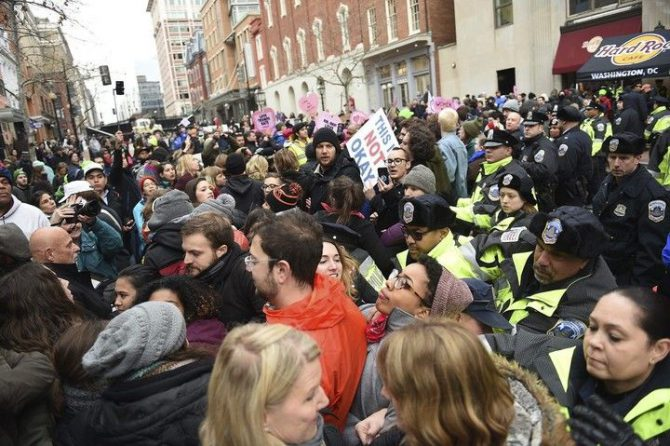 La policía ayuda a varias personas que trataban de asisitir al desfile de investidura y que han sido bloqueados por los manifestantes ubicados en la avenida Pennsylvania, en protesta contra el presidente de Estados Unidos.