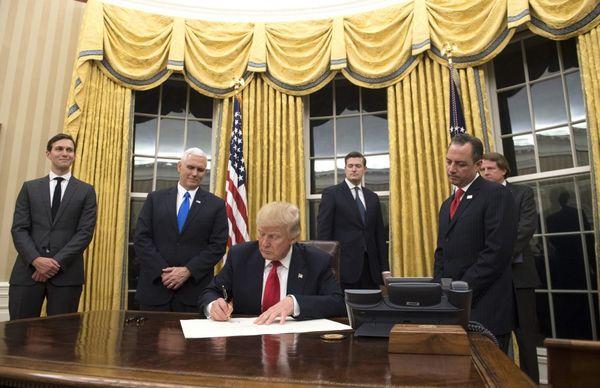Trump firmando su primera orden ejecutiva contra el Obamacare.