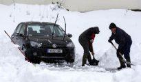 Dos personas retiran la nieve acumulada en su vehículo y despejan la estrada a su casa en la localidad navarra de Espinal