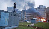 Un hombre observa un coche incendiado desde un muro donde se lee «La Policía mata», en el suburbio parisino de Bobigny